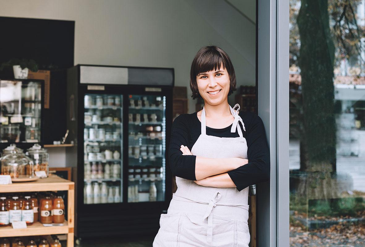 Verkäuferin eines kleinen Cafés steht in der Tür. Thema: Lokale Händler