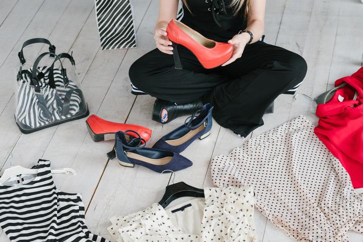 Frau sitzt umringt von Kleidungsstücken auf Fußboden.