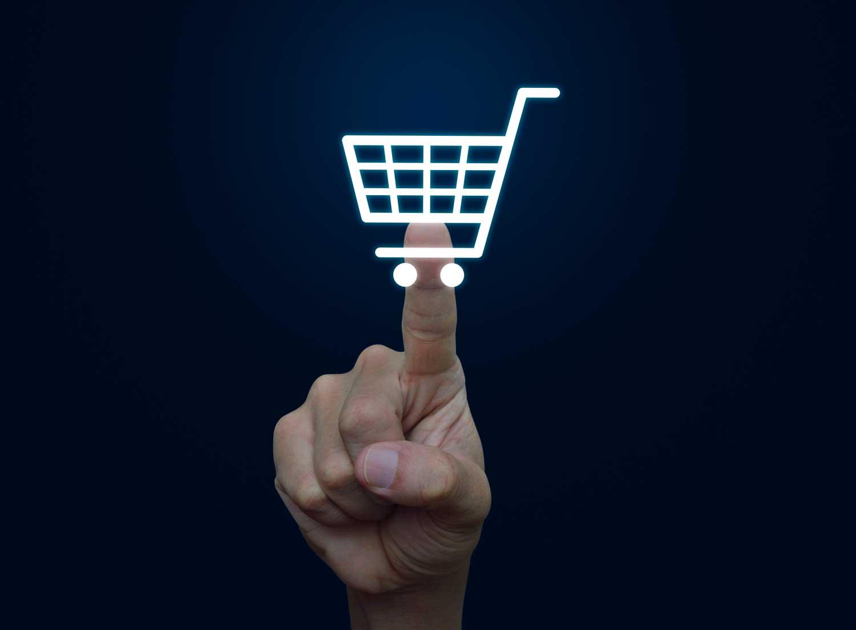 Zeigefinger deutet auf Einkaufswagen-Symbol.