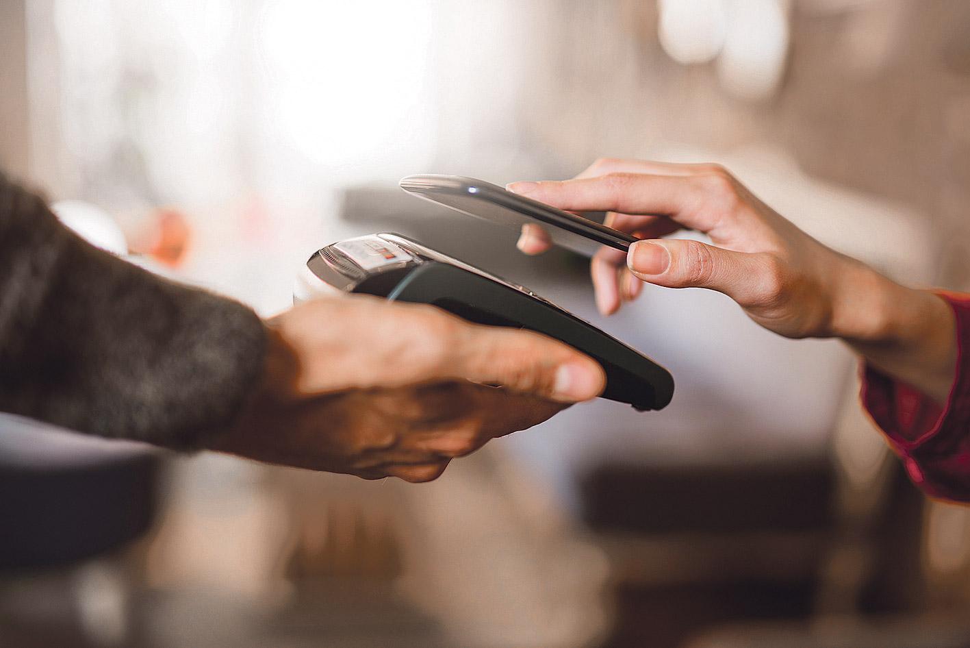 Smartphone wird an ein Bezahlgerät gehalten.