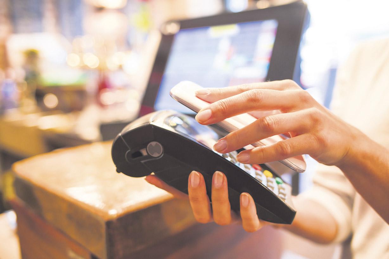 Frau nutzt neue Payment-Methode an der Kasse.