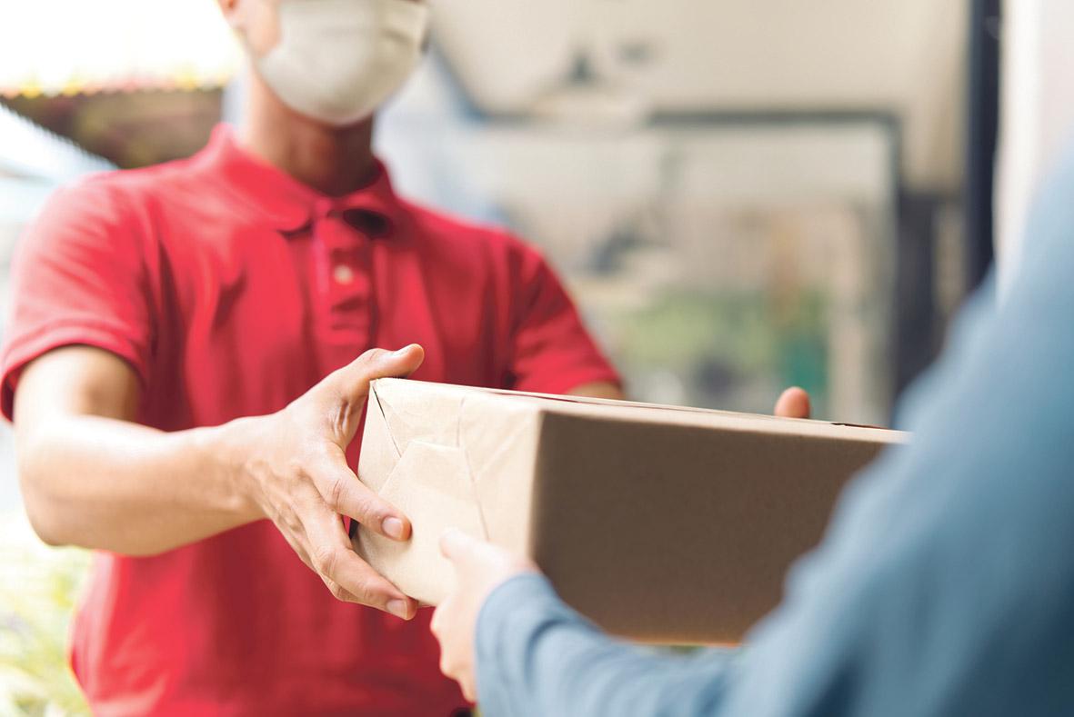 Ein Paketzusteller mit Mundschutz übergibt ein Päckchen.