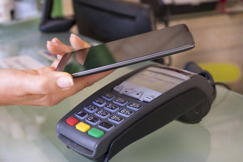 Kundin hält Handy an Kartenlesegerät, um zu bezahlen.