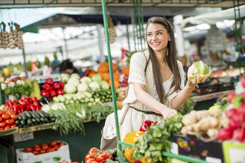 Frau kauft Gemüse auf einem Wochenmarkt ein.