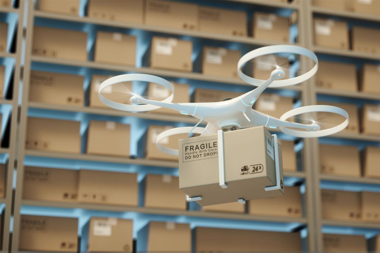 Fliegende Drohne mit Paket in einem Logistiklager