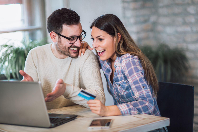 Glückliches Pärchen am Laptop; die Frau hat eine Kreditkarte in der Hand. Thema: Erlebnisshopping