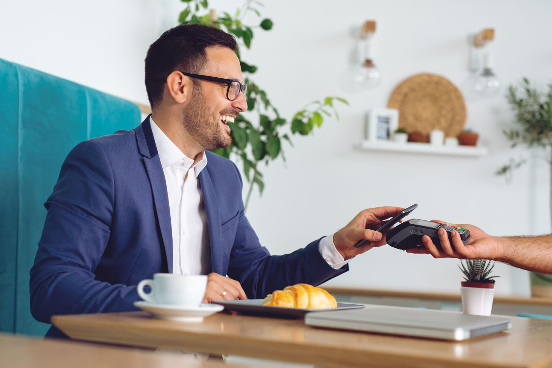 Geschäftsmann bezahlt sein Frühstück im Café mit dem Smartphone. Thema: Pay by mobile