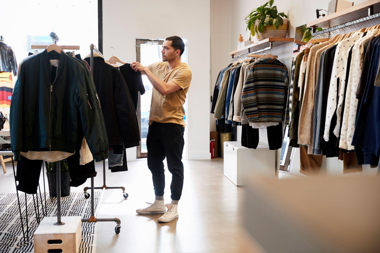 Kunde steht im Laden und schaut sich Kleidungsstücke an. Thema: stationärer Handel