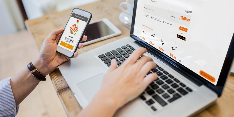 Käufer hält beim Online-Einkauf sein Handy in der Hand, um sich mit Fingerabdruck zu authentifizieren.