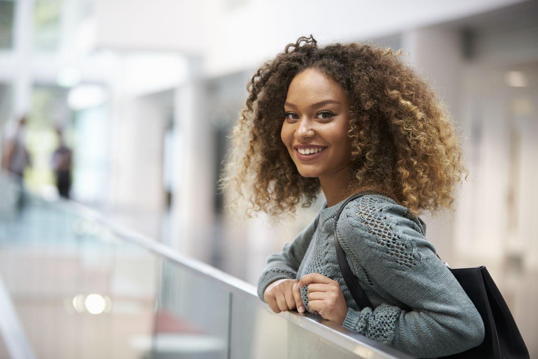 Eine lächelnde junge Frau. Eine Karriere im Einzelhandel ist für Absolventen eine attraktive Perspektive