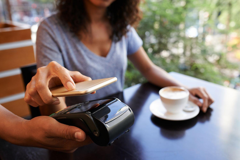 Eine Frau bezahlt kontaktlos ihren Kaffee. Die Technologien im Einzelhandel mehren sich