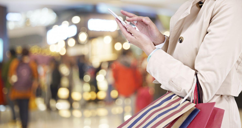 Frau schaut beim Einkaufen auf ihr Handy.