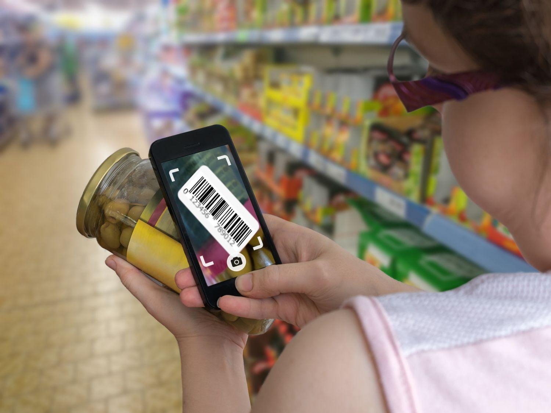Eine Frau fotografiert mit ihrem Smartphone den Barcode auf einem Glas Oliven ab. Die digitale Transformation hat viele Gesichter