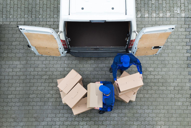 Lieferanten entladen Pakete aus einem Minibus. Thema Logistik im Einzelhandel